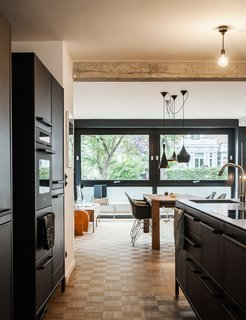 For their kitchen, Fabian and Dorothee Heine selected a steel countertop to contrast the matte-black island and cabinets from Vipp. At mealtimes, the family gathers at a Bigfoot table from e15, which is surrounded by vintage Eames shell chairs.
