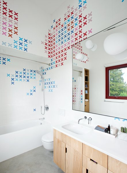Husband-and-wife ceramic artists, Dear Human, baked x-shaped decals into store-bought Olympia Tile before arranging them in the kids' bathroom. The tub is by Bette and the sink, set in a Corian countertop, is by Duravit.