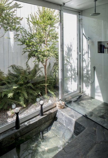 The bathroom is poured-in-place concrete surfaced in laja stone, a local material chosen by the architect to evoke the region's thermal baths. The space opens to a private garden via two doors—one in the shower, the other behind the toilet. The shower fittings are from Paini.