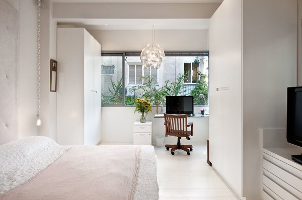 On the other side of the apartment, a bedroom doubles as a workspace.  Bedroom from Open-Plan, Personality-Filled Apartment in Tel Aviv