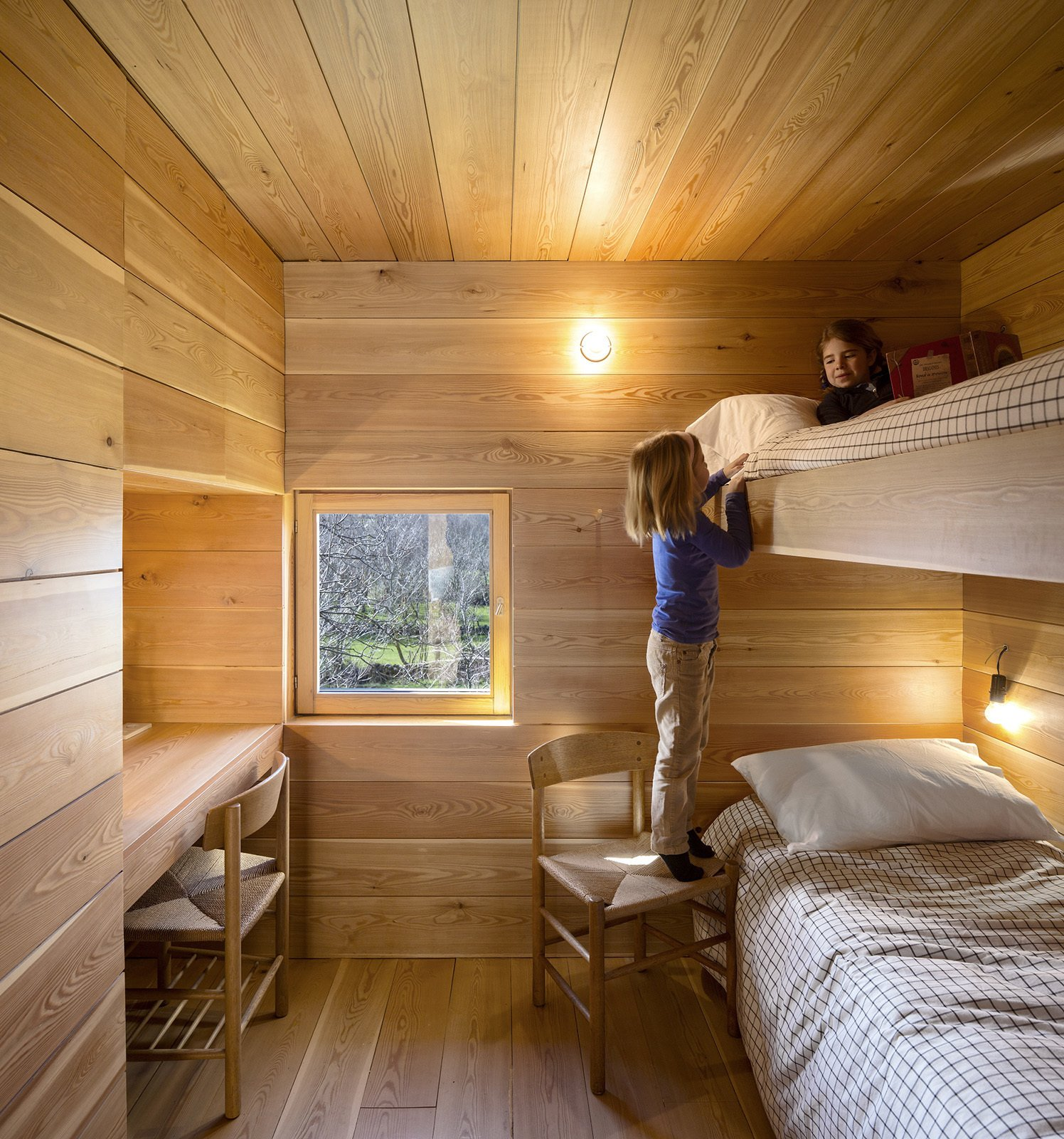 The kids room is outfitted with built-in bunk beds. Tagged: Kids Room, Bedroom, Medium Hardwood Floor, and Bed.  Refuge by Diana Budds from Creative and Cozy Countryside Homes