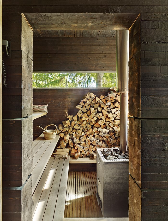 Shed & Studio A wood-burning stove from Harvia, of Finland, heats the sauna. The pavilion's rough-cut pine walls are treated with tar, a preservative that yields a time-worn aesthetic.  Photo 10 of 10 in 10 Sterling Saunas in Modern Homes from How a 1,000-Year-Old Technique Made This Pavilion