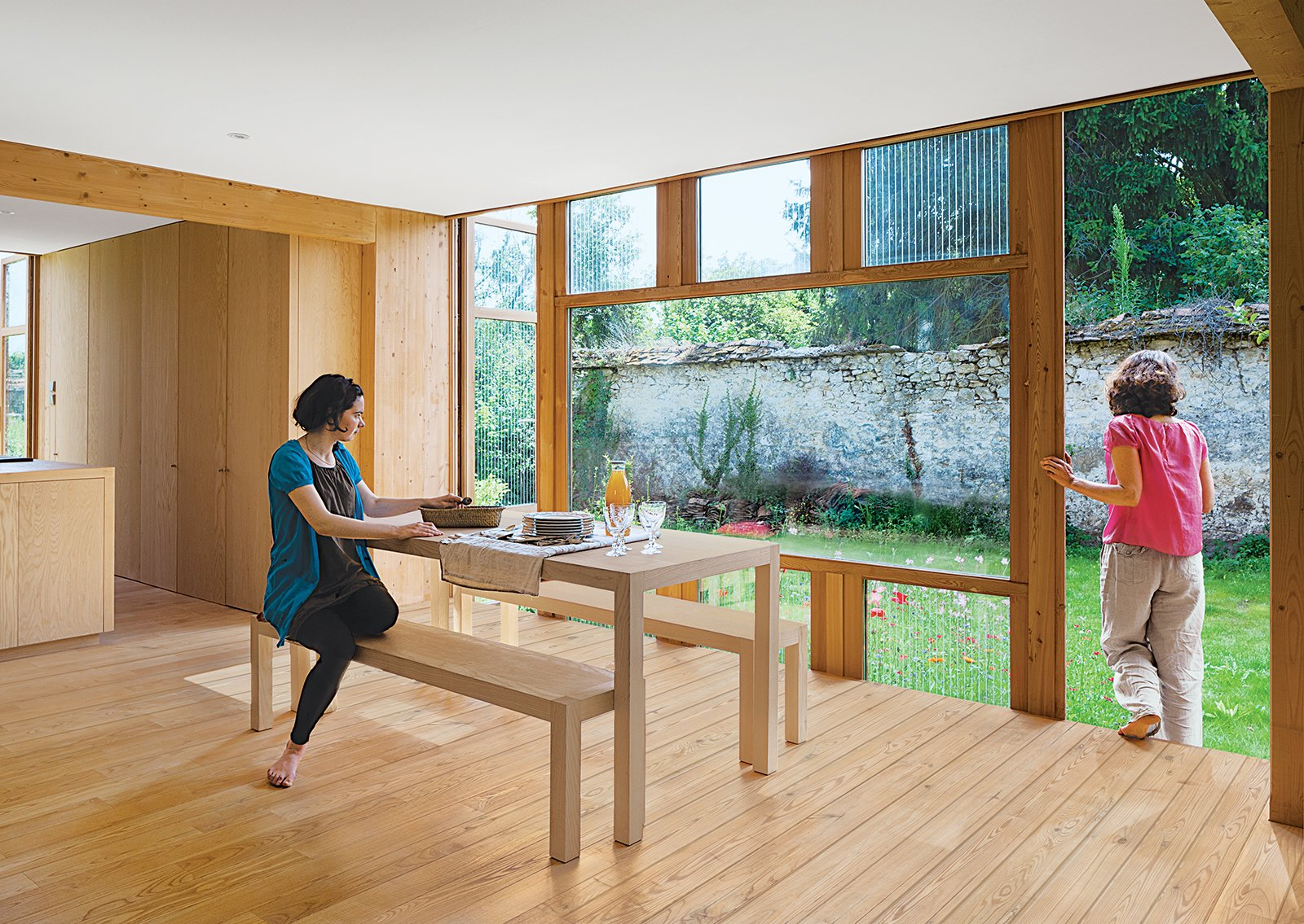 Glass doors printed with a serigraphy technique (above) are on two sides of the house. Jacquot sits at a dining table and benches designed by Arba and built by Menuiserie Ressy. Tagged: Dining Room, Light Hardwood Floor, Table, and Bench.  Photo 4 of 4 in Eco-Friendly A-Frame in the French Countryside