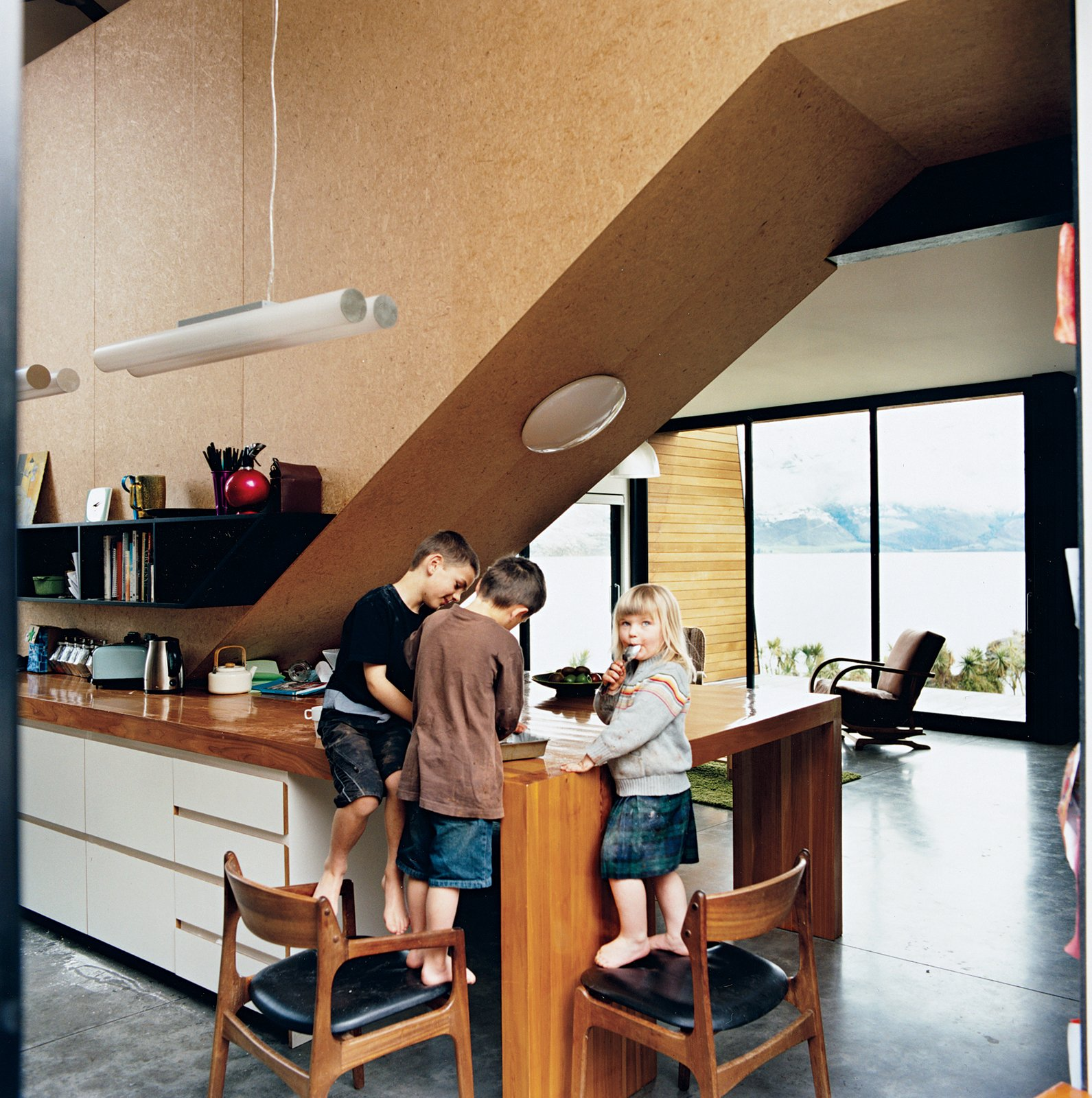 "The kids, Archie, Linus, and Olive, stand in the kitchen, beneath the strand board–clad stairwell that leads to the bedrooms. Kerr and Ritchie initially envisaged rich materials for the interior, but changed their minds in favor of what they call a ""cartoony"" approach with cheaper, hard-wearing elements. ""We didn't want the space to feel too grown-up,"" Kerr says.  Photo 5 of 12 in Nature Nurtured"