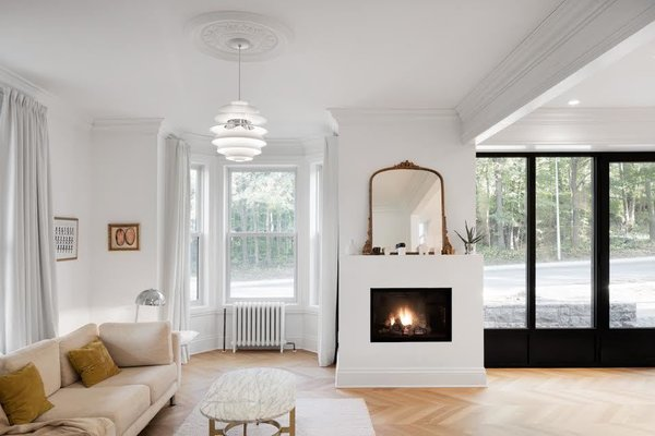 """The ceiling moldings were kept to create a sense of intimacy, and to blend the home's classical style with the modern look of the kitchen,"" architect Maxime Moreau says. A PH Snowball light pendant by Louis Poulsen illuminates the living room, and a gas fireplace by Foyer Universel keeps it warm, with a mirror above the fireplace allowing light to bounce around the space."