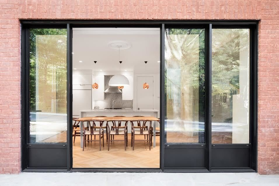 The owners requested that an enlarged passageway connect the dining room to a new outdoor space on the home's south facade, which Moreau and his team achieved with a 15-foot opening and French doors. A clay brick veneer replaces the existing brick exterior.  Ideas for reno from This House Looks Great After 107 Years