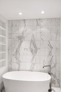 The master bathroom's Wetstyle bathtub, paired with a Kohler faucet, sits up against calacatta marble tiles on the wall.