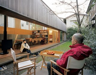The entire interior wall opens, extending the house visually and socially into the small garden that lies between the multigenerational family's two homes. The boys' favorite feature is the soccer goalpost (which doubles as clothesline).