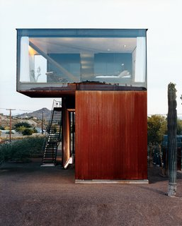 The glass-enclosed master bedroom floats above the corrugated, oxidized steel exterior.