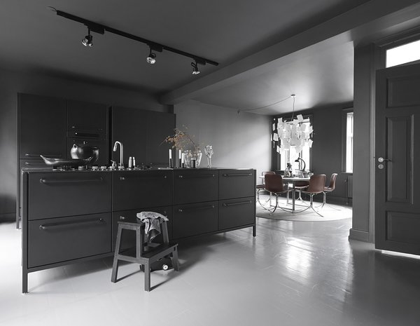 """""""The kitchen is the room we use the most,"""" Sofie says. The dark gray walls and tonal accents make it cozy and cave-like, while natural illumination and light-toned accessories introduce airiness and circulation. Even in the colder months, the Egelunds spend most of their time there, and Sofie maintains that the stark darkness makes it a homey place to entertain guests and spend time with the family. """"And,"""" she adds, """"you can always go to the other floors if it gets too dark!"""" The kitchen island, shelves, glass, and ceramics are by Vipp."""