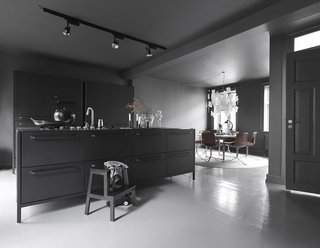 """The kitchen is the room we use the most,"" Sofie says. The dark gray walls and tonal accents make it cozy and cave-like, while natural illumination and light-toned accessories introduce airiness and circulation. Even in the colder months, the Egelunds spend most of their time there, and Sofie maintains that the stark darkness makes it a homey place to entertain guests and spend time with the family. ""And,"" she adds, ""you can always go to the other floors if it gets too dark!"" The kitchen island, shelves, glass, and ceramics are by Vipp."