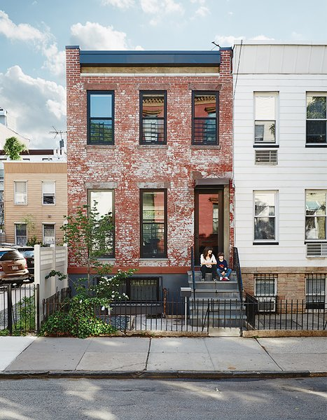 """Margarita McGrath and Scott Oliver of Noroof Architects termed the 1,650-square-foot house in Greenpoint, Brooklyn, """"Pushmi-Pullyu,"""" in reference to the interior-exterior flow they created. Resident Jill Magid, pictured on her front steps with son Linus, is a conceptual artist; she fabricated the neon house numbers."""
