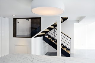 The kitchen island, illuminated by Flos Smithfield ceiling lamp, faces the steel entry stair, framed through a window. The steel was stripped and painted, and new L-shaped wood treads, steel railing, and wood handrail were subsequently fitted.