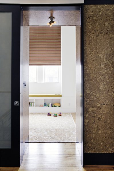 On the second floor, the sliding door to one of the kids' bedrooms lies flush with a cork-wrapped wall. In the bedroom, a colorful custom Maharam window shade rests above a window seat with a Kvadrat cushion.