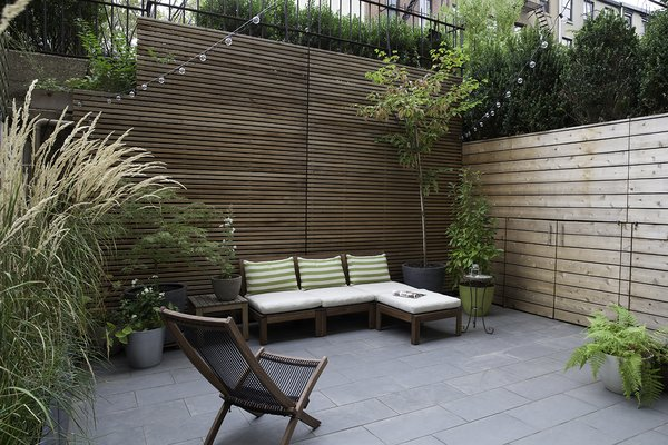 The living room leads to a private outdoor patio. Before the renovation, the slightly below grade area was in plain sight to passersby, as it lays adjacent to the public walkway into the building. This less-than-ideal setup was addressed in the redesign by adding a slatted cedar perimeter fence, along with tall trees and shrubs. Clever hidden doors conceal patio storage under the entry walkway.