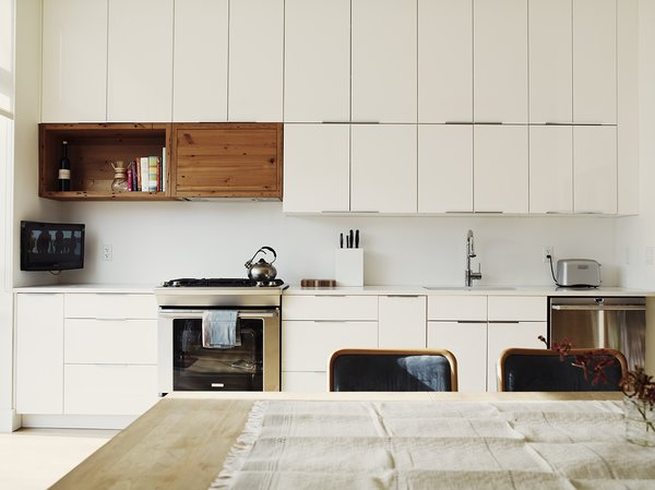 On the first floor, the kitchen features simple white IKEA cabinetry juxtaposed with a natural wood surround for the hood, also repurposed from the original fir beams.