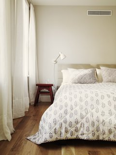 The master bedroom features shorter planks of five-and-a-half-inch-wide white oak flooring. Their warmth is enhanced by the wall color, Benjamin Moore Abalone, the only departure from white anywhere in the house. The bed is from CB2, and side table is from Environment 337.