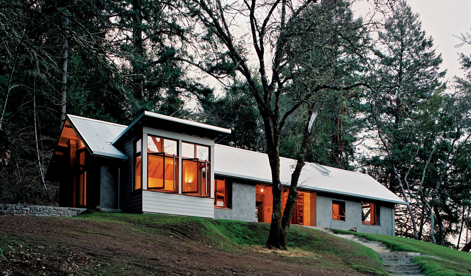 """Outdoor, Slope, Trees, and Woodland Ever aware of context, architect Henry Siegel says of his house, """"A lot of architects' buildings look better on a pedestal than in context. Our design would look out of place on a pedestal—we placed it so it really fits its specific site.""""  Photo 3 of 5 in Hay Is for Horses, Straw Is for Houses"""