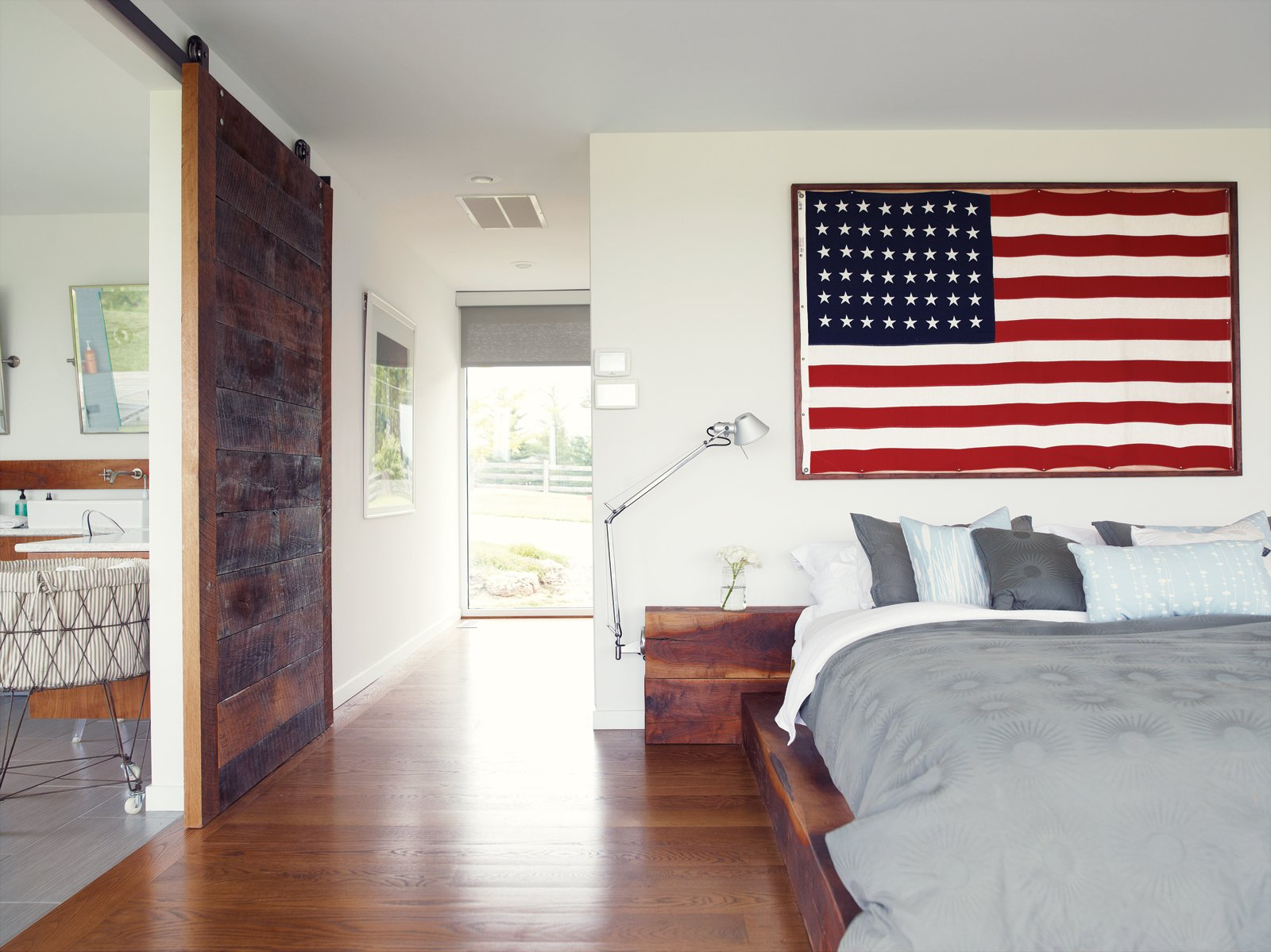 Bedroom, Medium Hardwood Floor, and Bed He built the walnut bed and nightstands in the master bedroom with the help of Hannah's two brothers. One of his clients at his hair salon gave him the American flag; the bedside lights are Tolomeo classic wall lamps by Artemide. The bed linens are   from Inhabit. A sliding barn door rolls sideways to reveal the bathroom.  Week in Review: 7 Great Reads You May Have Missed June 1, 2013 by Megan Hamaker from Material Focus: Custom Walnut Designs