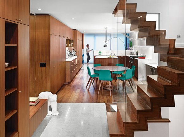 Architect Drew Mandel updated a house in Toronto to look modern and cozy. The clients desired a warm material base for the interior so Mandel used American walnut for the flooring, millwork, and staircase. Loire limestone covers the landing below the steps and Calacatta marble clads the kitchen counters and island.