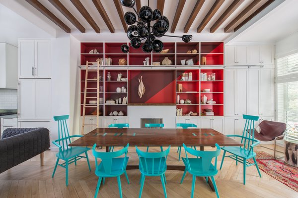 A quartet of red paints (Raspberry Truffle, Million Dollar Red, Vermillion, Arroyo Red), all by Benjamin Moore, make the built-in shelving in the dining area pop. The table is a custom design made of bookmatched walnut slabs joined by lacquered butterflies. The chairs are vintage Paul McCobb lacquered in turquoise (Benjamin Moore's Aruba Blue). The Ligne Roset Ruché sofa, designed by Inga Sempé, separates the living and dining spaces. The chandelier is by David Weeks Studio.