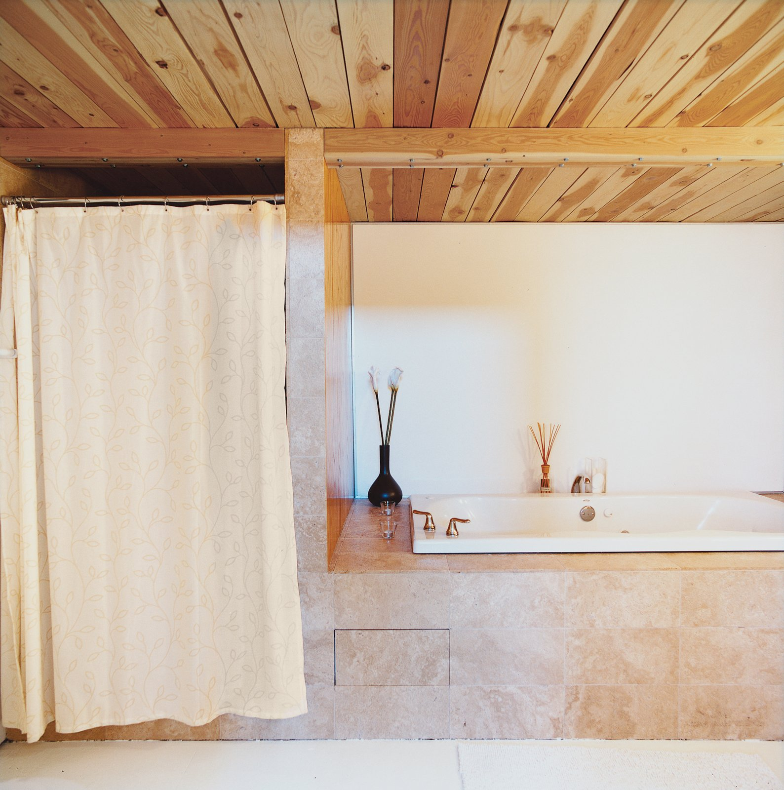 The master bathroom departs from the cool tones used throughout the house in favor of warmer, neutral-toned marble tiling, which wraps around a large soaking tub.  Photo 8 of 10 in A Minneapolis Building That Has Lived Multiple Lives Is Revitalized by a Coffeehouse Owner