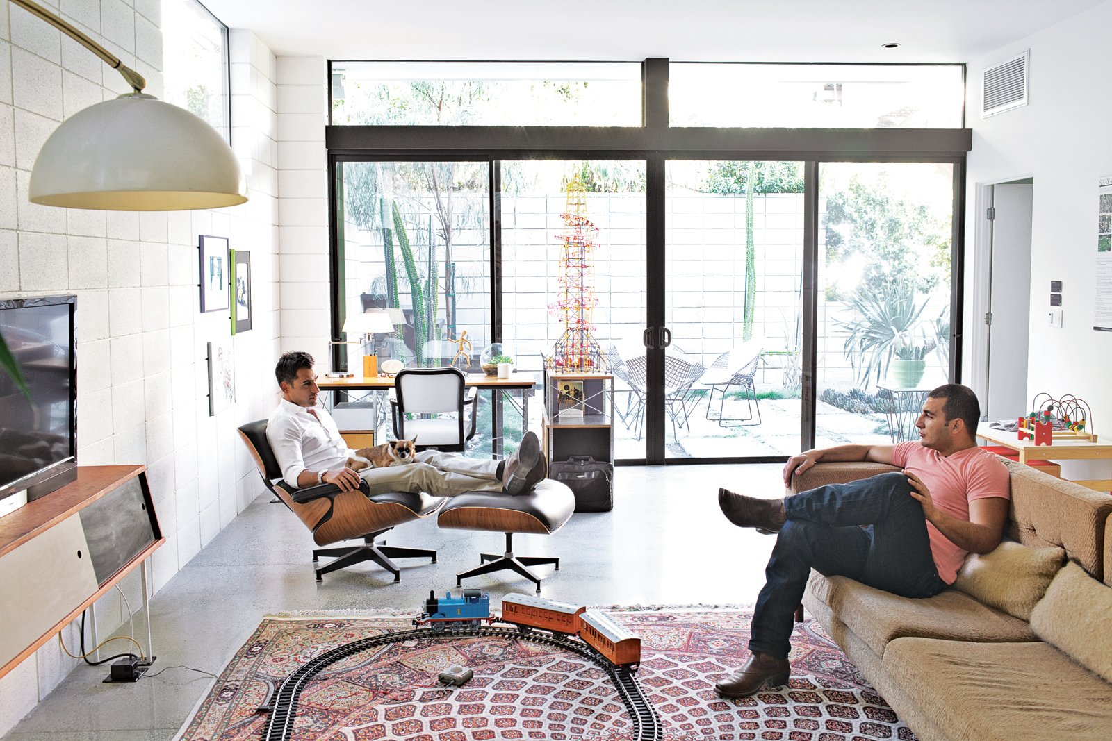 """Living Room, Recliner, Sofa, Floor Lighting, Concrete Floor, Console Tables, Ottomans, Rug Floor, Chair, Desk, and Recessed Lighting Brothers Nima and Soheil relax in the family room on an Eames lounge chair and a custom sofa they designed. """"Mid-century architecture draws the outdoor environment indoors,"""" says Soheil. """"There's a lot of natural light, a lot of ventilation.""""  Photo 3 of 54 in Eames Lounge Chair Porn from The First LEED Gold-Certified Family Home in San Diego"""