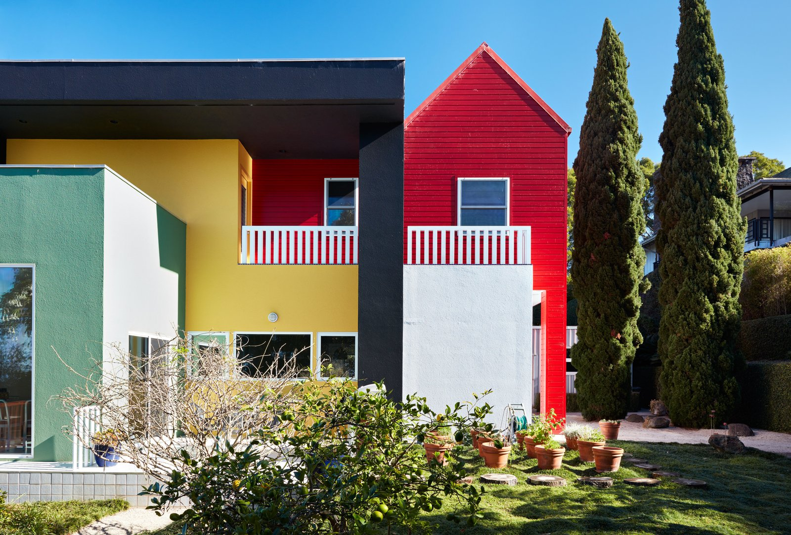 """Outdoor and Grass Though seemingly whimsical and freewheeling, Sottsass was exacting in his designs: He had forbidden the Olabuenagas from repainting the home's stucco facade, insisting that they let it """"metamorph into what it wants to be,"""" but the couple ultimately decided to restore its faded colors last fall, using new elastomeric Behr paints that were blended to original specifications.  Best Photos from Thank Sottsass for the Most Memphis House Imaginable"""