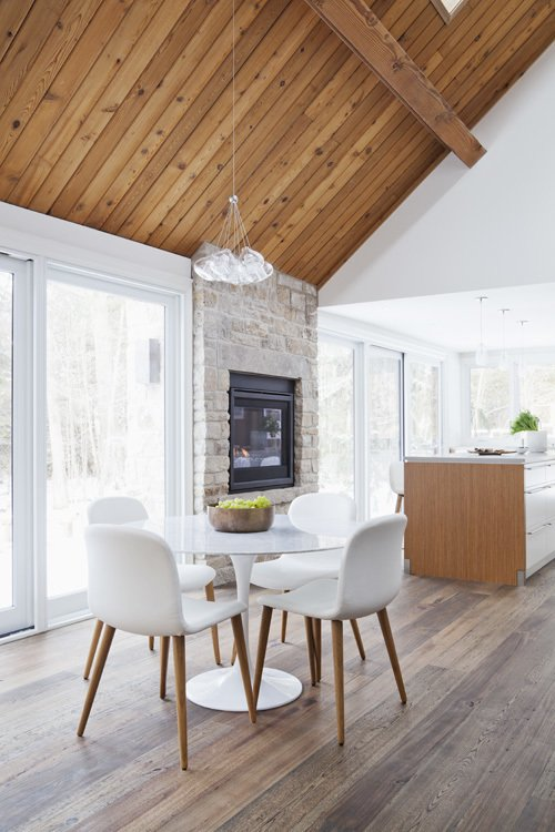 New skylights and a wall of windows fill the open-plan area with light. A two-way indoor/outdoor stone fireplace enhances the home's connection to nature.  Hard to Believe This Home Dates Back to the 1820s by Luke Hopping