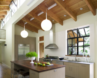 A row of clerestory windows run beneath the peaked ceiling in the kitchen, permitting natural light to bisect the heart of the home.