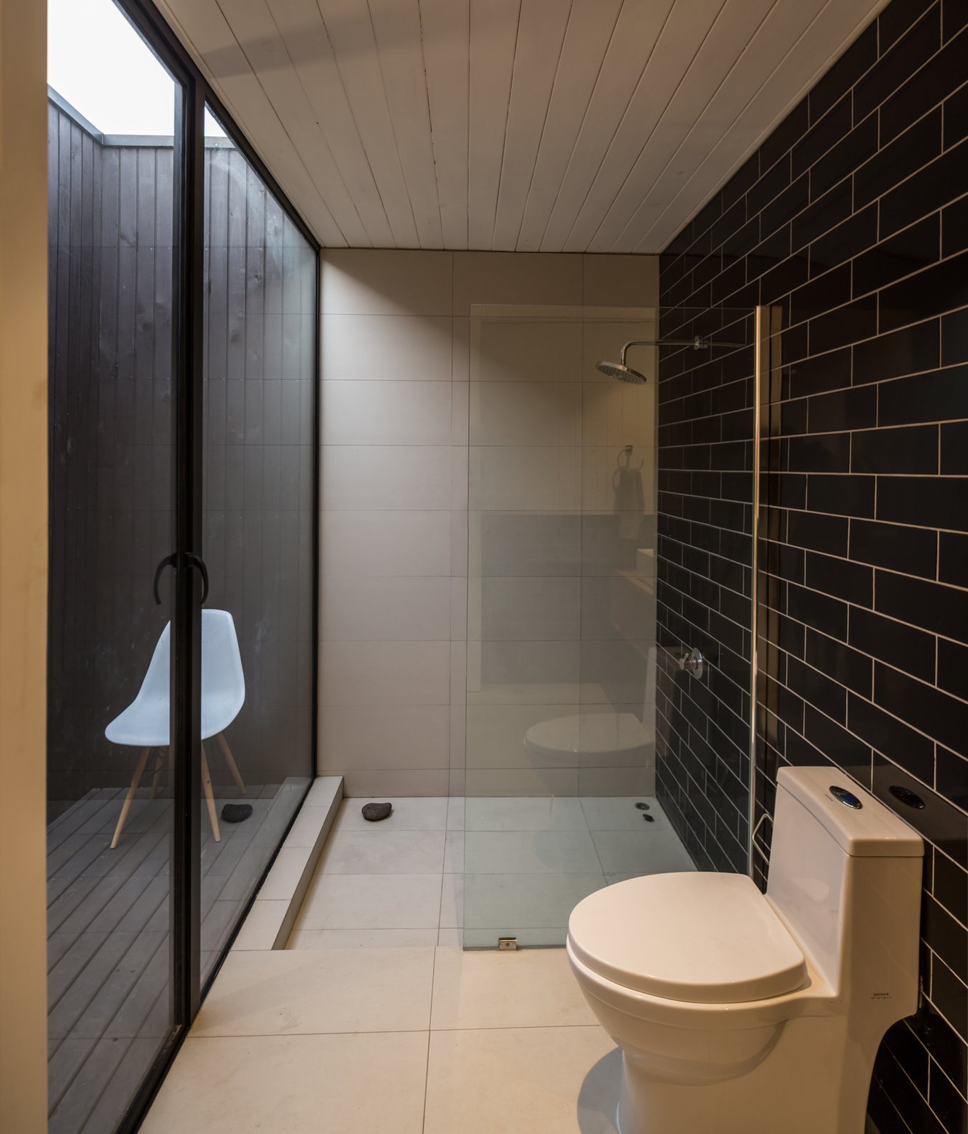 """""""The water waste from the shower and the kitchen irrigate the interior garden,"""" LLaumett says. """"The toilets have their own patio, which provides them with ventilation and natural light."""" Black Marazzi tiles cover the wall.  Unplugged by Kelly Dawson"""