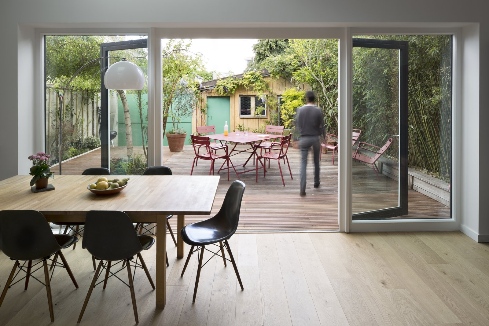 Dining Room, Table, Floor Lighting, Light Hardwood Floor, and Chair When the family wants to eat meals inside, they can sit around the dining table on Eames chairs.  Wisteria Residence by Kelly Dawson