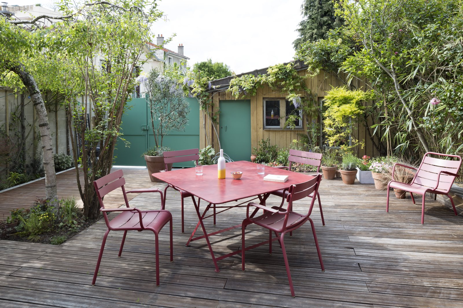 A dining set by Fermob, featuring Luxembourg chairs, makes alfresco meals easy.  Wisteria Residence by Kelly Dawson
