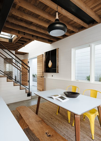 Throughout the house, Curtiss mixed natural materials with industrial ones. Downstairs, fir and cedar wood on the doors and open-joisted ceiling balance the colder, industrial feel of the concrete floor and steel staircase railing. In the dining room, a pendant lamp from RLM Lighting hangs above a table that combines Cherner table legs with a new white laminate top. The yellow chairs are by Tolix.