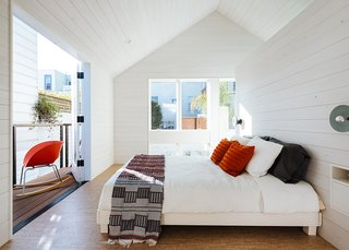 In the master bedroom, the gable roof and balcony foster the illusion of generous space. A free-standing wall divides the sleeping space from the bathroom.