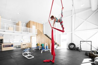 Here, the high ceiling, a style borrowed from industrial lofts, serves a utilitarian purpose. Gymnast rings hung overhead allow athletes to suspend themselves 25 feet in the air.