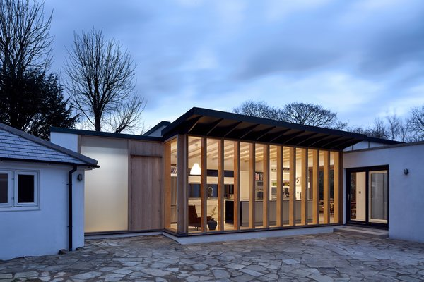 The new addition to this home has panes that open to a front courtyard, and another set of windows that face the rear garden. The majority of the building was pre-fabricated and finished on site.
