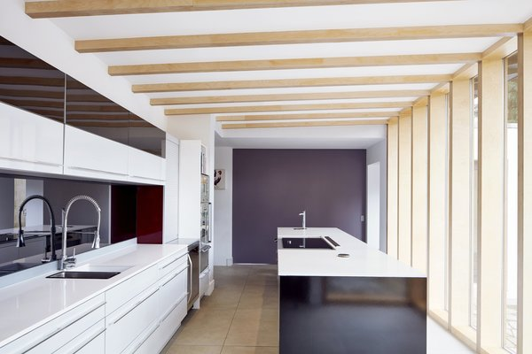 """Exposed beams continue into the kitchen ceiling, where minimal details and contrasting dark shades emphasize the natural materials. The window frames are positioned as """"fins"""" to draw in just enough southern-facing light to keep the room comfortable."""