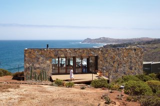 Dubbed Casa Cuatro, this stone-covered house designed by Barbara Bernal sits above a 180-foot cliff that overlooks the Pacific Ocean. The locally quarried stone makes the house blend in with the landscape and acts as a thermal-mass wall, absorbing heat during the day and releasing it through the evening.