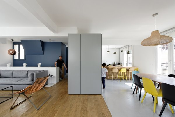 """The upper floor includes the entry, cloakroom, guest bathroom, kitchen, dining room, living room, and terrace,"" Hammer says. ""In contrast to the lower floor and its separated rooms, the living area is composed as an open space with no walls."" Nerd Chairs by David Geckeler for Muuto surround a handcrafted nutwood table in the dining room."