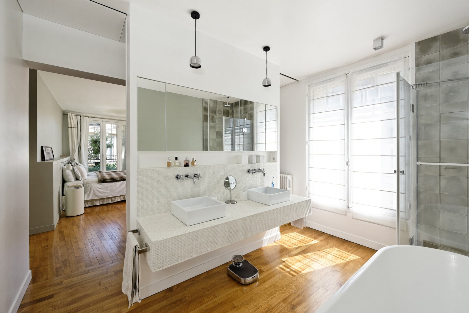 "Bath Room, Pendant Lighting, Vessel Sink, Mosaic Tile Wall, Freestanding Tub, Light Hardwood Floor, Corner Shower, and Tile Counter ""The old living room and balcony on the sixth floor were transformed into the master bedroom with an en-suite open bathroom,"" Hammer said. Flos lighting illuminates the space above the vanity.  Photo 3 of 11 in 10 Dreamy Parisian Homes from How Many Apartments Does it Take to Make One Home?"