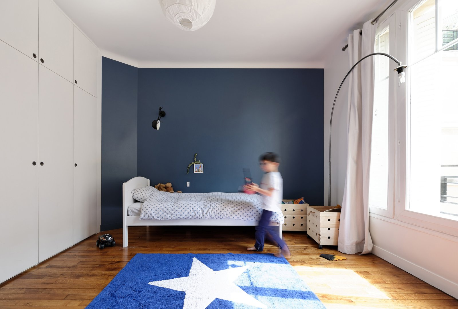 """Kids Room, Bedroom Room Type, and Bed """"All interior walls were removed to create four individual rooms on the sixth floor,"""" Hammer says. The two children and the new baby share a bathroom. And in their bedrooms, storage continues to be key.  Search """"paris landmarks architectural print unframed"""" from How Many Apartments Does it Take to Make One Home?"""