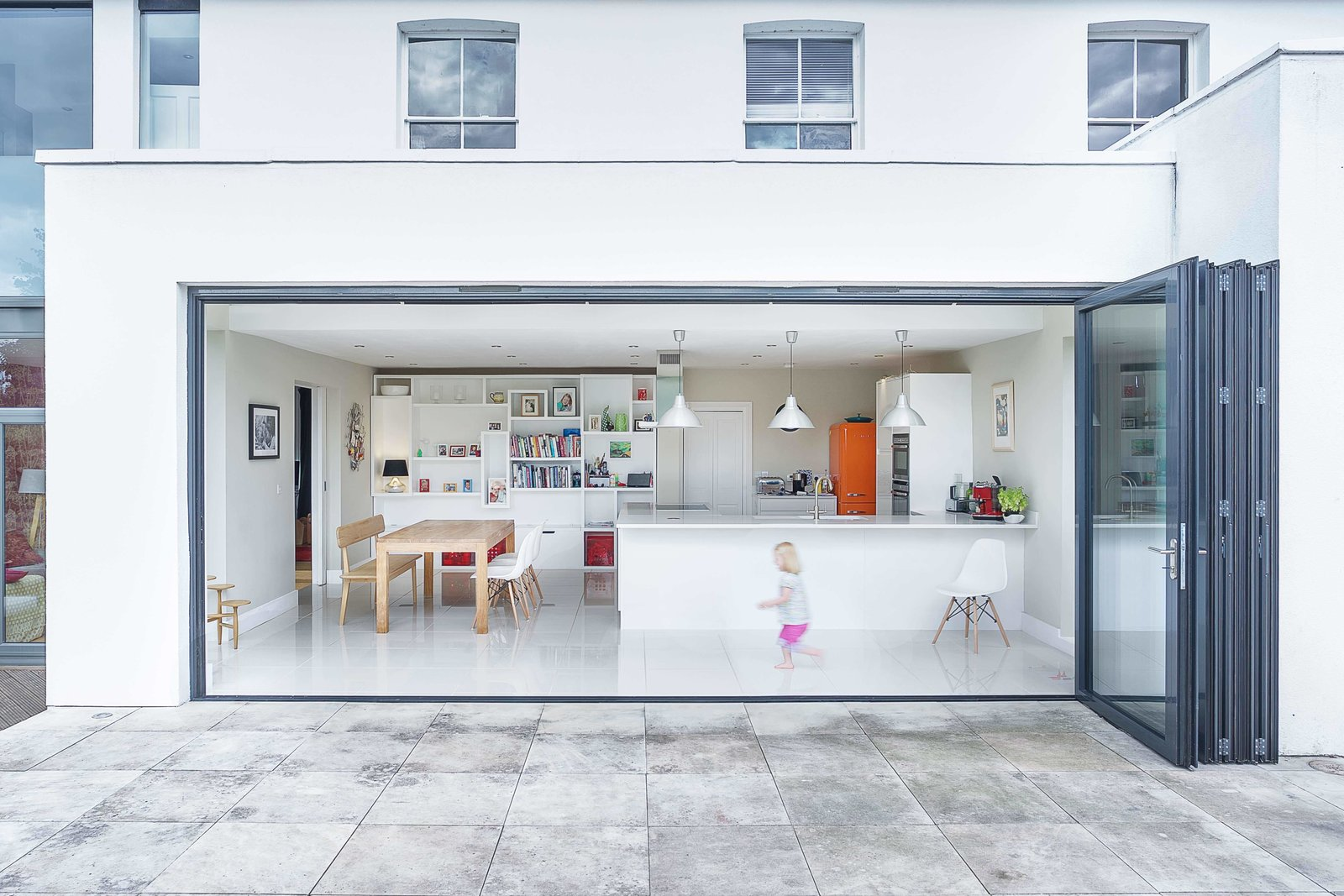 An enormous bi-fold door from Sun Paradise peels back to open the upgraded kitchen-dining area to a new raised terrace. The home's exterior is wrapped in an insulated render system.  Backyards & Decks from Think a Victorian Villa Can't Be Made Modern? Think Again