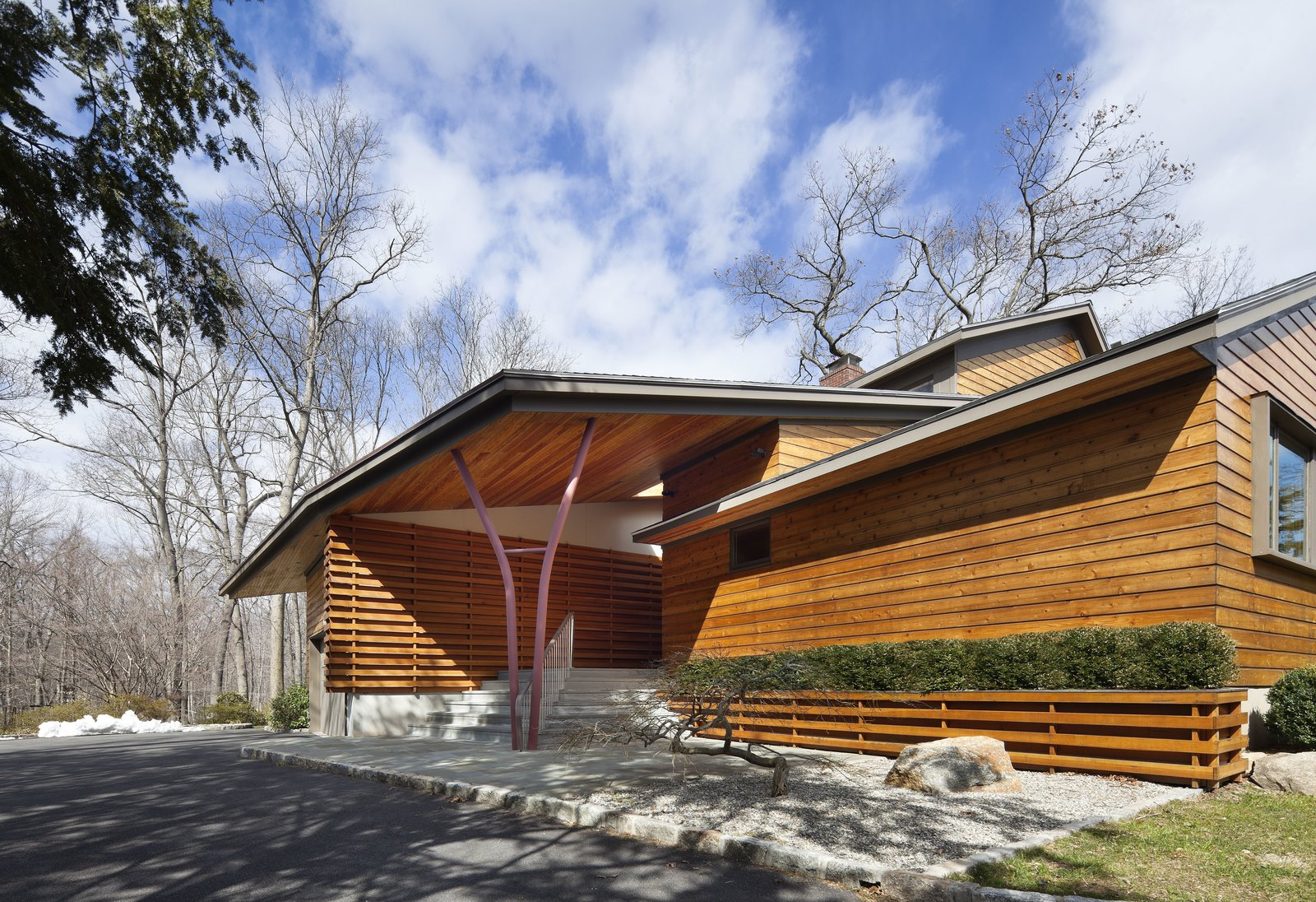 The Douglas fir slats cover the facade and are repeated throughout the rest of the house. Moser references the woods by a pair of steel beams on the front porch that allude to the silhouette of a tree.  Photo 1 of 7 in After a Fire, a Midcentury Home Rises from the Ashes