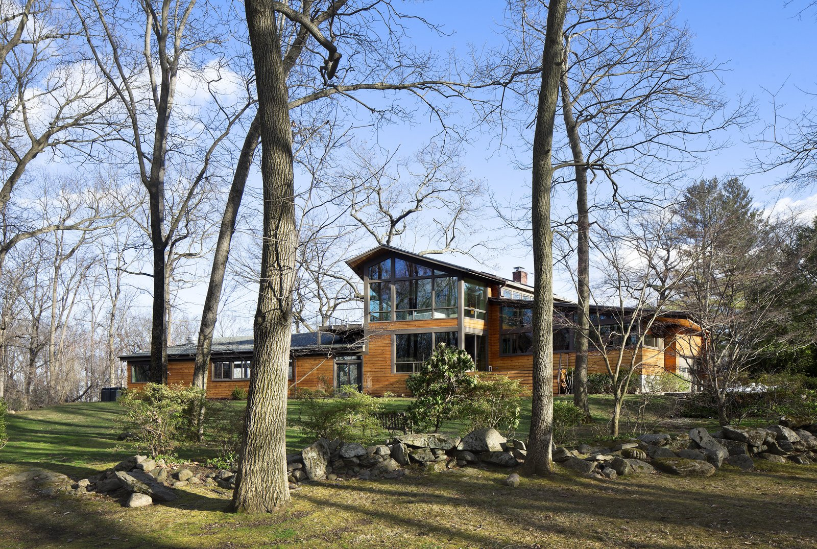When Moser first arrived on the site, the original home had almost no good views of the neighboring Saxon Woods. The solution was to build expansive Low-E windows to enjoy views of the woods.  After a Fire, a Midcentury Home Rises from the Ashes by Caroline Wallis