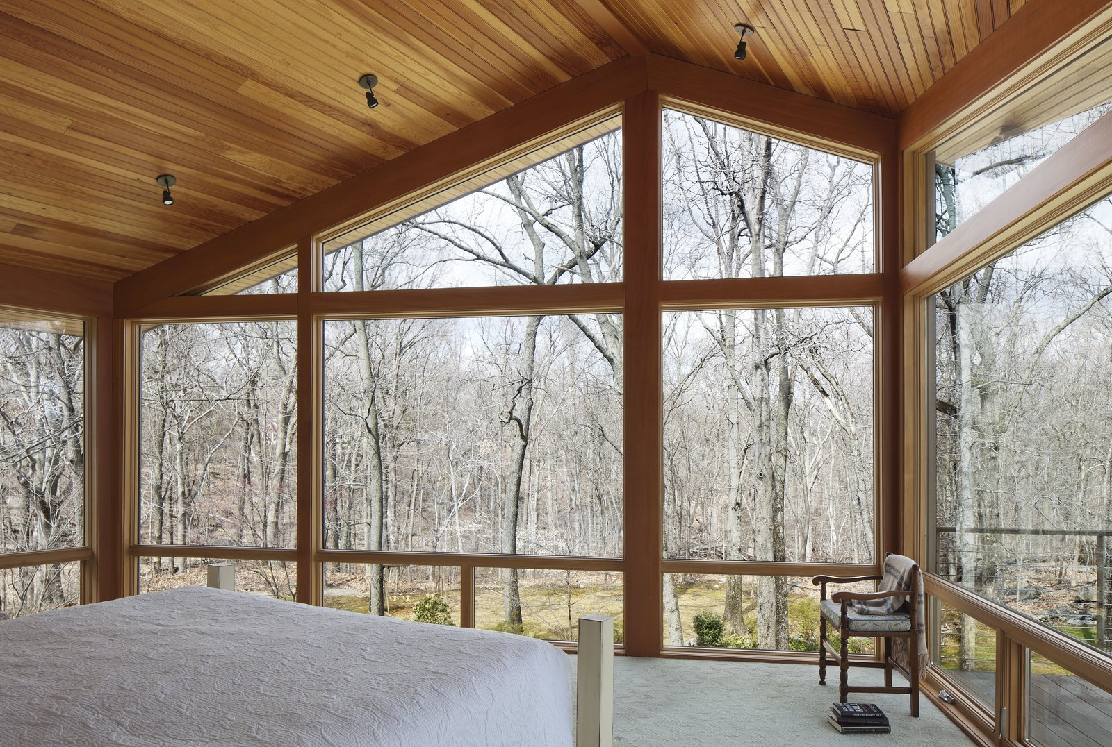 From the northeast corner of the master bedroom, the homeowners can walk out onto a deck area to enjoy the view of the woods.  Bedroom from After a Fire, a Midcentury Home Rises from the Ashes