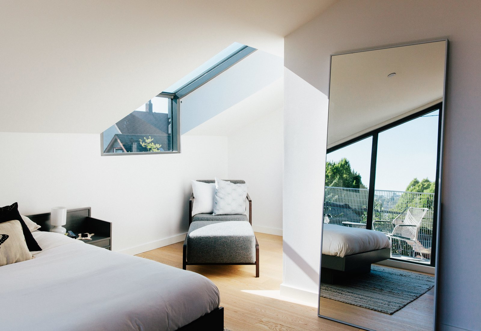 Bedroom, Bed, and Light Hardwood Floor Dick Hellofs and Karli Gillespie occupy a new house at the back of the site. Light streams into their bedroom through a Spectrum Skyworks skylight, shining on an armchair and ottoman from Calligaris, while an IKEA mirror reflects a refurbished 1960s bed.  Best Photos from As Housing Costs Soar, Two Homes Multiply to Seven