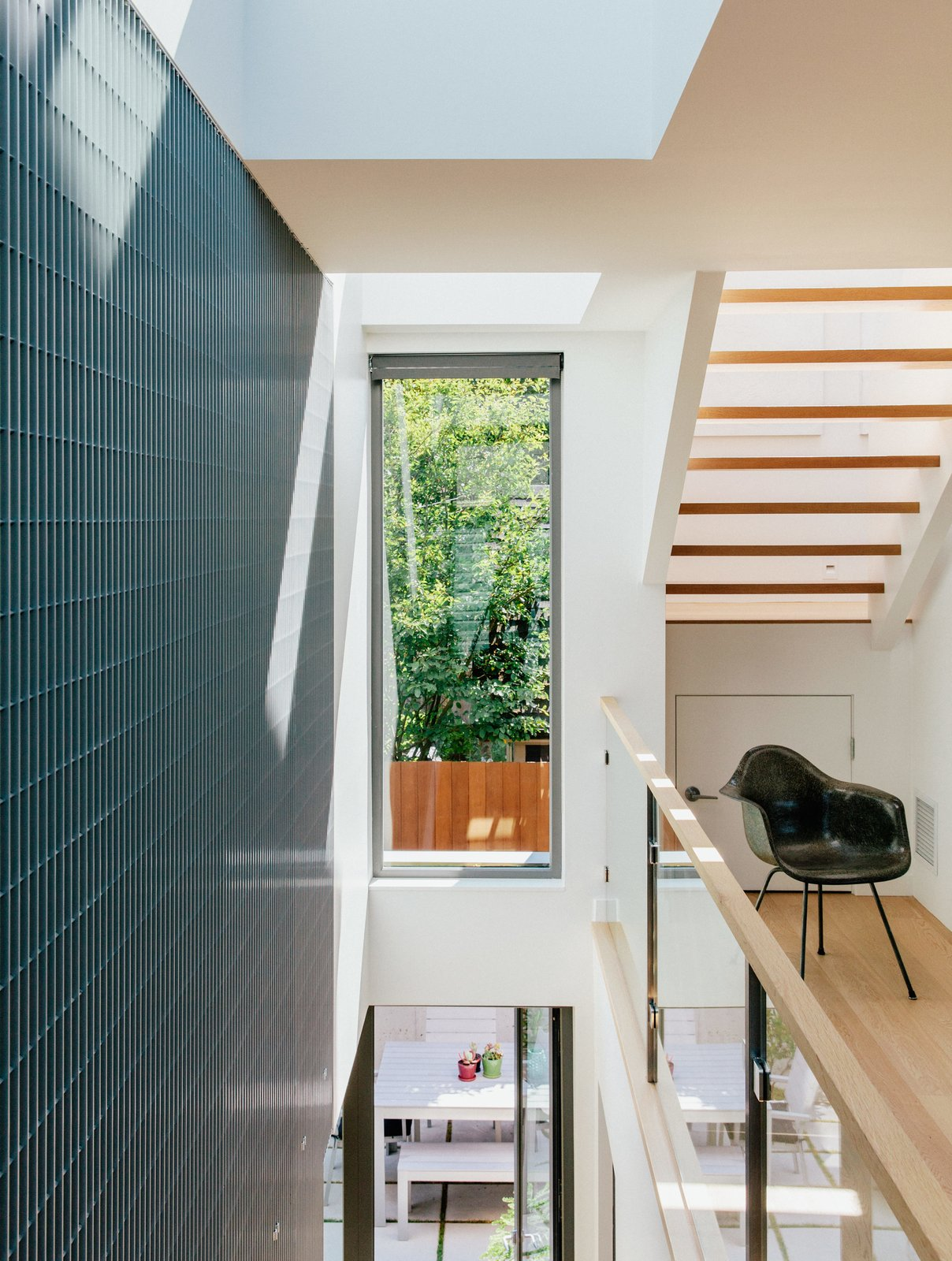Staircase and Wood Tread The laneway house features Kentwood engineered-wood floors, Cascadia windows, and aluminum-bar grating. The Eames DAX chair is vintage.  Best Photos from As Housing Costs Soar, Two Homes Multiply to Seven