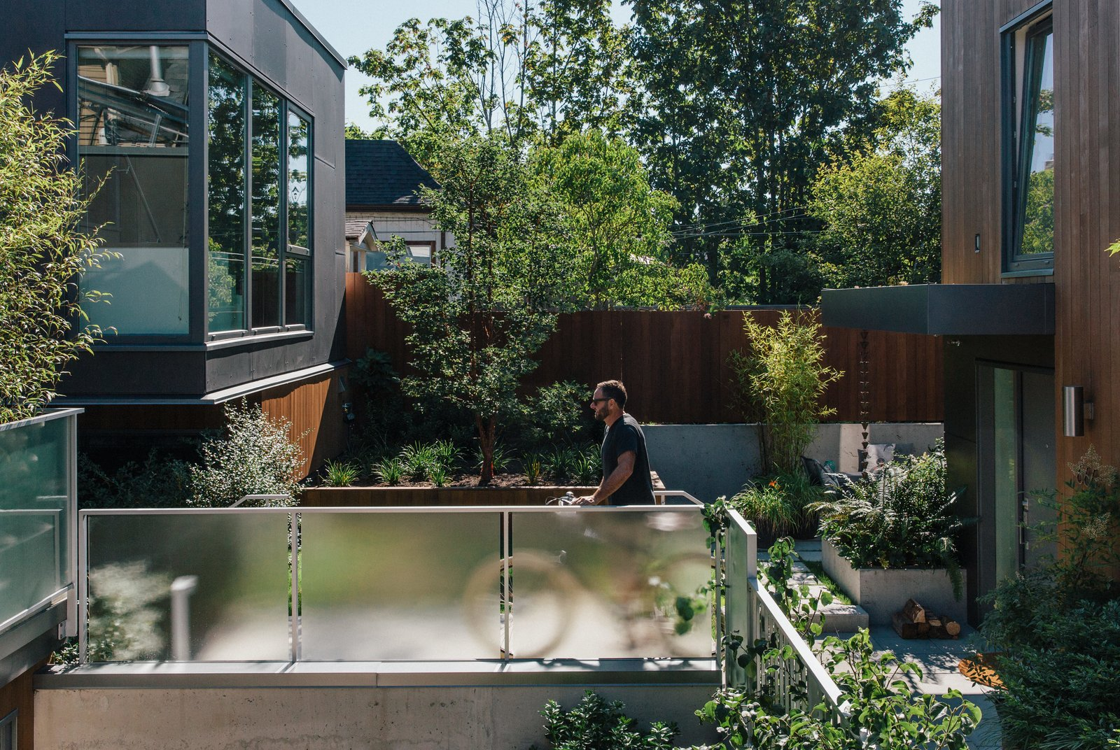 """Outdoor, Walkways, and Side Yard The """"mid-ground"""" between the three structures serves as a community hub. Dick takes advantage of the site's shared bicycle storage and its proximity to a popular bike lane.  Best Photos from As Housing Costs Soar, Two Homes Multiply to Seven"""