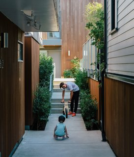 Resident Misha Bukowski plays with young Zachary in the walkway between the renovated buildings. The new units are clad in stained local cedar.